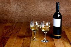 Bottle of white wine and two glasses Stock Images