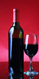 Bottle of Wine. And Wine Glass on red background stock photos