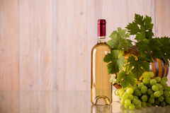 Bottle of wine with a barrel. And grapes and grapeleaves stock image