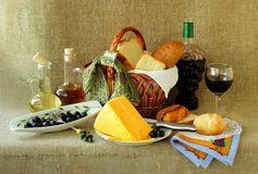 Bottle of wine, a basket of bread, cheese and olives Royalty Free Stock Photos