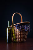 Bottle of wine and basket with grapes. Bottle of wine and basket with blue wet ripe Isabella grape bunches on dark background; copyspace Royalty Free Stock Image