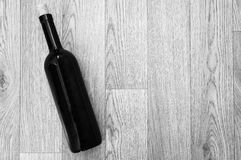 Bottle of wine on black-and-white wooden table Stock Image