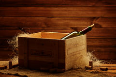 Bottle of wine in box in wooden interior Stock Image