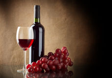 Bottle of wine and a bunch of red grapes. A bottle and a glass of red wine and a bunch of red grapes on linen background Royalty Free Stock Photo