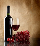 Bottle of wine and a bunch of red grapes. A bottle and a glass of red wine and a bunch of red grapes on linen background Stock Image