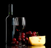 Bottle of wine, a bunch of red grapes and a piece of cheese. A bottle and a glass of red wine, a bunch of red grapes and cheese on black background Royalty Free Stock Images