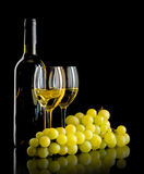 Bottle of wine and a bunch of white grapes. A bottle and a glass of white wine and a bunch of white grapes on black background Stock Image