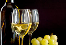 Bottle of wine and a bunch of white grapes. A bottle and a glass of white wine and a bunch of white grapes on black background Royalty Free Stock Photography
