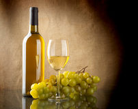 Bottle of wine and a bunch of white grapes. A bottle and a glass of white wine and a bunch of white grapes on linen background Royalty Free Stock Photography
