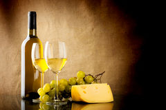 Bottle of wine, a bunch of white grapes and a piece of cheese. A bottle and a glass of white wine, a bunch of white grapes and cheese on linen background Stock Photos