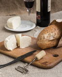 Bottle of wine, cheese and bread are on sacking. Bottle of wine, cheese and white bread are on sacking Stock Photography