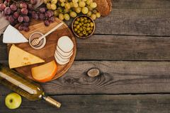 Bottle of wine and cheese on cutting board Stock Photos