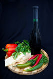 Bottle of wine, cheese, pepper and parsley. Stock Photography