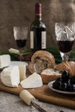 Bottle of wine, cheese and white bread are on sacking. Bottle of wine, olives, cheese and white bread are on sacking Royalty Free Stock Photo