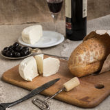 Bottle of wine, cheese and white bread are on sacking. Bottle of wine, olives, cheese and white bread are on sacking Royalty Free Stock Image