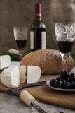 Bottle of wine, cheese and white bread are on sacking. Bottle of wine, olives, cheese and white bread are on sacking Stock Photos