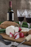 Bottle of wine, cheese and white bread are on sacking. Bottle of wine, cheese, vegetables and white bread are on sacking Stock Photography