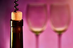 A bottle of wine with a cork. And a corkscrew on a background of blurred glasses. Copy space Royalty Free Stock Photography
