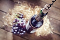 Bottle of wine, cork and corkscrew on wooden table royalty free stock photography