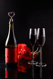 Bottle of wine with a cork in the form of heart and two glasses of three red gerbera Stock Photos