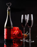 Bottle of wine with a cork in the form of heart and two glasses of three red gerbera. Stock Images