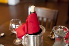 Wine chilling on table. Bottle of wine with cork wrapped in red napkin on a table with glasses Royalty Free Stock Photo
