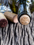 Bottle of wine and corks on wooden table. Royalty Free Stock Images