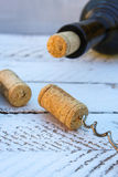 A bottle of wine and a corkscrew in the cork on wooden background Royalty Free Stock Image