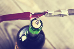 Bottle of wine with corkscrew on wood Royalty Free Stock Photography