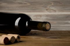 Bottle of wine with corkscrew on wooden background royalty free stock photo