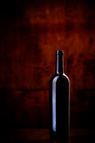 Bottle of wine on dark red background. Bottle of wine with light reflections on dark red background Royalty Free Stock Photo