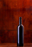 Bottle of wine on dark red background. Bottle of wine with light reflections on dark red background Royalty Free Stock Images