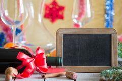 Wine and  blackboard. Bottle of wine and decorations next to empty blackboard for your text on wooden table. Christmas or New Year`s drink Royalty Free Stock Images