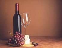 A bottle of wine an empty glass bunch of red grapes a slice of cheese on a dark background. Copy space. Selective focus. royalty free stock photos