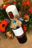 Bottle of wine with flower decoration. Bottle of red wine with flower decoration Royalty Free Stock Photos