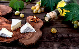 Bottle of wine, fresh grape, cheese and walnut on wooden background Stock Photos