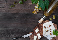 Bottle of wine, fresh grape, cheese and walnut on wooden background Royalty Free Stock Photos