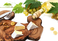 Bottle of wine, fresh grape, cheese and walnut on wooden background Stock Image