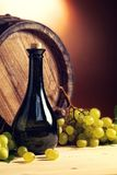 Bottle of wine in front, wine barrel and white grapes. Stock Photo