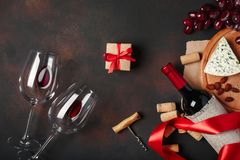 Bottle of wine, gift box, blue stinky cheese, red grapes, almonds, corkscrew and corks, on rusty background top view stock images
