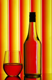 Bottle & wine glass. Vibrant stripe background reflecting through clear bottle and stemless wine glass stock photo
