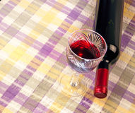 Bottle of wine and a glass. Against a background of bright cloth Stock Photo