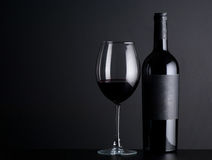 Bottle of wine with a glass on a black background Royalty Free Stock Photos