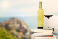 Bottle of wine and glass on books against sea view Royalty Free Stock Photography