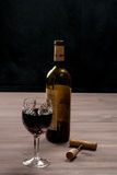 A bottle of wine with a glass, cork and a corkscrew. On a wooden table Royalty Free Stock Image