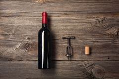 Bottle of wine with wine glass and gift box on wooden background. Top view with copy space for your text stock photography