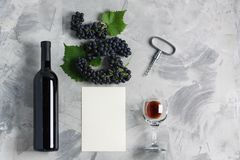 Bottle of wine glass grape corkscrew empty card mockup. Bottle and glass of wine grape with leaves, corkscrew, white empty card mockup for your logotype or text royalty free stock image