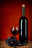 Bottle of wine, glass and grapes over red Royalty Free Stock Image