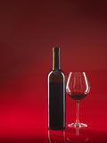Bottle of wine, glass on red background Royalty Free Stock Photography