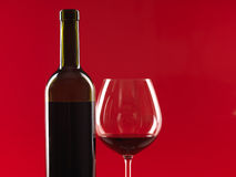 Bottle of wine, glass on red background Stock Images